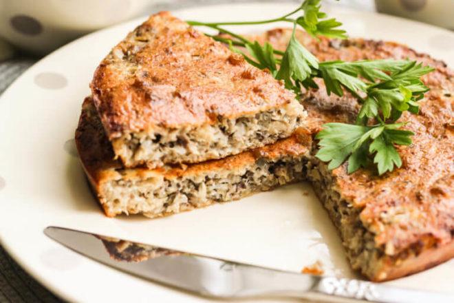 рыбный пирог на белой тарелке и нож